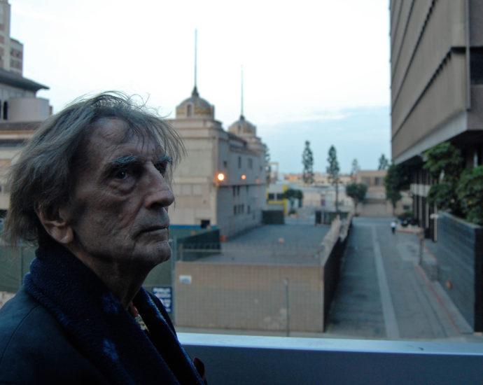 Harry Dean Stanton walking in the street